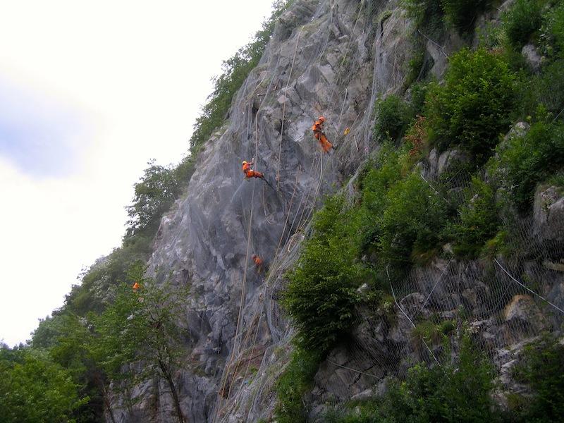 Uomini appesi a una corda che stendono le reti paramassi su una parete franosa sopra una strada